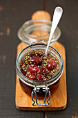Pickled kalamata olives with oregano in glass jar on a chopping board