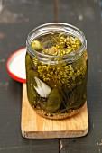 Gherkins in a glass jar on a chopping board