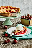 Cherry pie with a lattice top on a cake stand and on a plate with vanilla ice cream