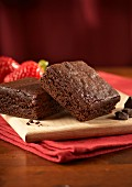 Two chocolate brownies with strawberries