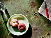 Peaches on a plate next to a newspaper and fruit knife