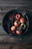 Organic red apples, carob pods and autumn leaves in a basket