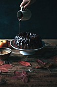 Chocolate ganache being poured onto a carob and apple Bundt cake on a cake stand