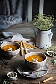 Creamy pumpkin soup in bowls on a rustic wooden table