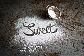 The word 'sweet' written in icing sugar