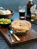 A whole steak pie in a casserole dish