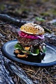 A burger with red onions and wild mushrooms