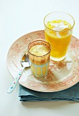 Glasses of mango lassi and pineapple smoothie on a plate