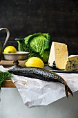 An arrangement of smoked mackerel, lemons, cheese and savoy cabbage