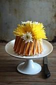 Yellow Cake mit Blumen auf Kuchenständer