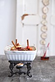 Bratpafel mit Zimtstangen und Zieräpfeln in Auflaufform auf Vintage Stövchen