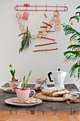 Christmas table decorated with hyacinths and amaryllis in vintage cups, stollen fruit cake, espresso pot and garland of dried apple slices and cinnamon sticks on wall