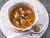 Vegetable soup with matzah balls and chicken breast
