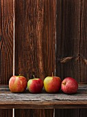 A row of fresh apples on a wooden table