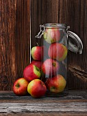Fresh apples inside and next to a glass storage jar