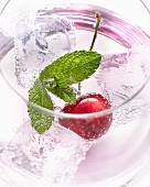 A glass of water with a cherry, ice cubes and mint