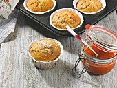 Freshly baked rose hip muffins with rose hip jam in a preserving jar