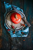 Hokkaido pumpkin with a knife and rose hips on a wooden board