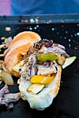 A street food sandwich with yellow pepper, courgette and meat