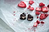 Vegane Zartbitterpralinen in Herzform, gefüllt mit Vanillecreme und gefriergetrockneten Erdbeeren