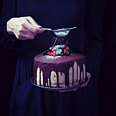 A woman's hand dusting icing sugar over a vegan chocolate cake decorated with fruits