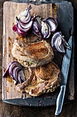 Pork chops and onions on cutting board with knife