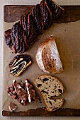 A chocolate babka swirl cake, chocolate bread and a chocolate bar with nuts on a rustic background
