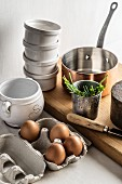 Soufflé ingredients: eggs, salt and chives together with soufflé dishes and a copper saucepan