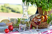 Carafe of water, bread basket, cheese and grapes on set picnic table