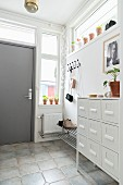 weiße Schubladenkommode in hellem Flurbereich mit Garderobenleiste und grauer Eingangstür