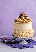 Kuchen mit Buttercreme, Popcorn, Schokoriegel und Erdnussbutter verziert