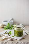 A jar of homemade salsa verde made with parsley, capers, garlic and olive oil