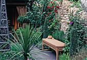 Sitzbank vor Steinmauer mit ROSE UND CLEMATIS,