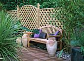 Gartenbank vor Holzgitter als Sichtschutz