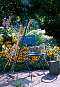 Gartenwerkzeug an blauen Stuhl gelehnt