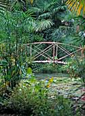 Brücke aus Holz und Bambusstäben über einen Teich