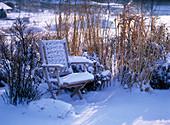 Garten im Winter mit verschneiten Gräsern, Stauden, Holzstuhl