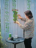 Holzwand mit Hilfe einer Schablone mit Efeuranken bemalen