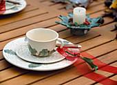 Tasse herbstlich dekoriert mit Ilexblatt, Kiefernnadeln, Hagebutten