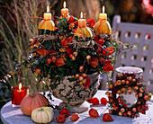 Zierkürbisse als Kerzenhalter auf Efeupflanze