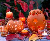 Cucurbita / Kürbisse ausgehöhlt und mit Sterndekor, Herbstlaub und Kerzen