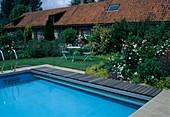 Swimmingpool, kleine Sitzgruppe auf dem Rasen, Beet mit Rosa (Rosen), Alchemilla (Frauenmantel), Leucanthemum (Margeriten), Nepeta (Katzenminze) und Sträuchern