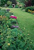 Staudenbeete säumen Rasenfläche mit Blick auf Haus, Phlomis(Brandkraut), Hemerocallis (Taglilien), Salvia nemorosa (Steppen-Salbei, Ziersalbei), Achillea (Schafgarbe)