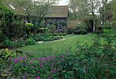 Landhausgarten im Frühling, Blick über Rasen auf Haus und Beet