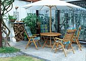 Sitzgruppe unter Sonnenschirm auf Terrasse am Haus, Brennholz-Stapel, Datura syn. Brugmansia (Engelstrompete) in der Ecke