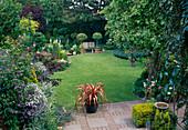 Stadtgarten mit ueppigem Staudenbeet, Gehoelzen, Kuebelpflanzen, Bank, Terrasse geht nahtlos in Rasenfläche über