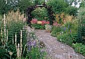 Weg mit Beton-Steinen und Platten gepflastert in reich bepflanztem Garten