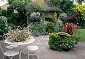 Terrasse mit Sitzgruppe, Kübelpflanzen und Vogeltränke
