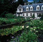 Landhaus mit rechteckigem Gartenteich, Nymphaea (Seerosen) und Wassersprudler , Beet mit Stauden : Campanula Glockenblumen), Hemerocallis (Taglilien)