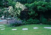 Kleine Terrasse mit hoelzernem Pavillon , Rosa ' Lykkefund'(Ramblerrose , Kletterrose) einmalbluehend mit gutem Duft, Nepeta (Katzenminze), Buxus (Buchs) Kugeln und Hecke, Fraxinus (Esche) Stamm, Platten als Trittsteine im Rasen